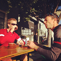 Two men in bicycle jerseys sitting outside at table having coffee